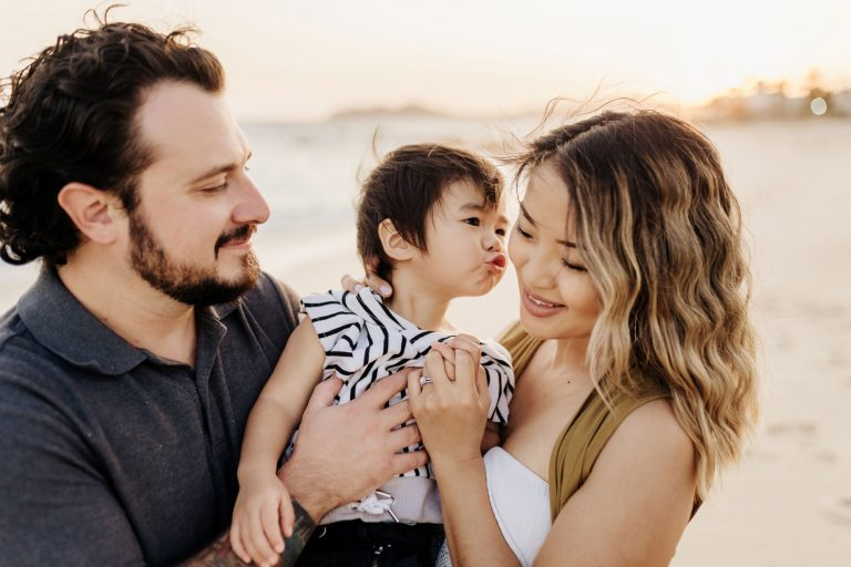 family with boy kissing the mom